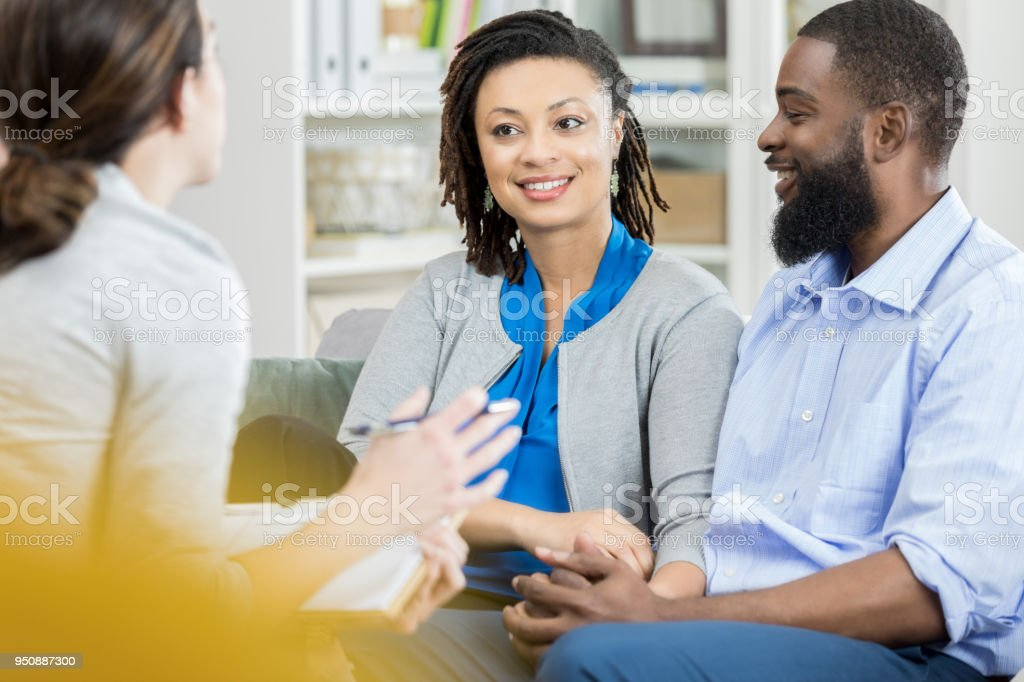 Mid adult couple talk with counselor stock photo