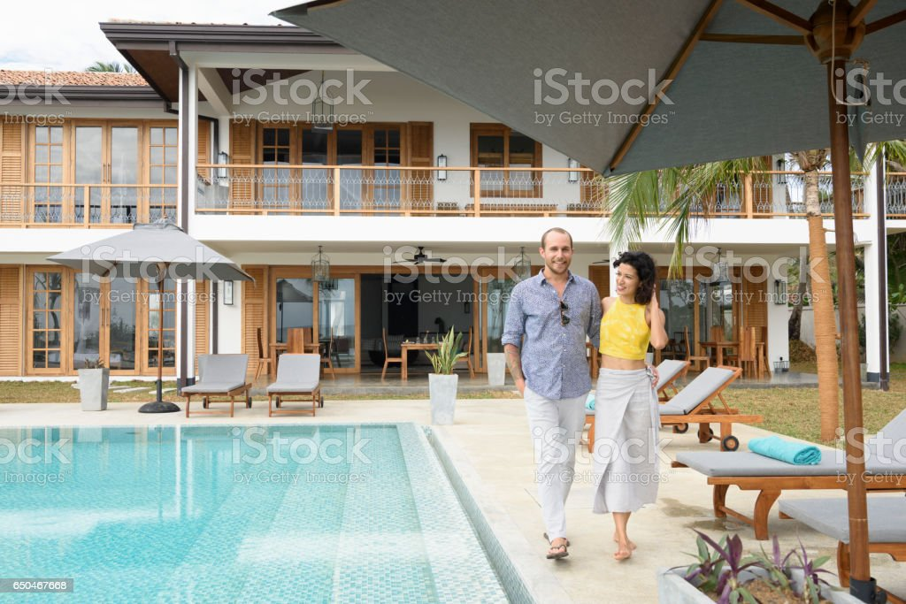 Mid adult couple walking next to swimming pool on vacation stock photo
