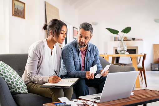 Mature couple calculating bills at home using laptop and calculator. Multiethnic couple working on computer while calculating finances sitting on couch. Mature indian man with african american woman at home analyzing their finance with documents.