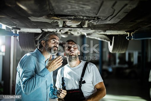 Male manager and auto mechanic examining undercarriage of a car in a workshop.