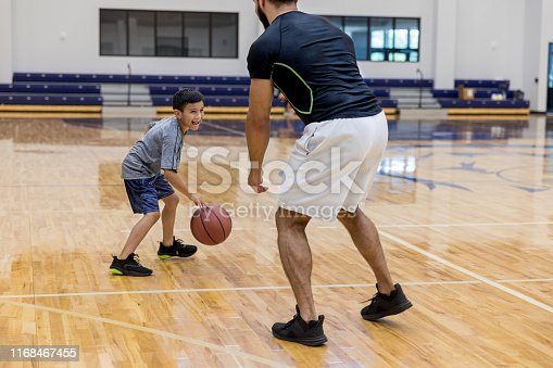 Mid adult dad spends time playing a one-on-one basketball game with his young son at the gym.