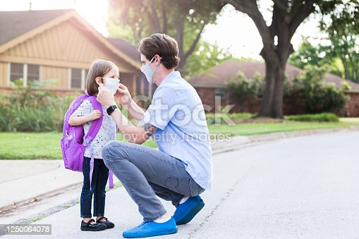 On the way to school, the mid adult father stops in the street to help his elementary age  daughter with her protective mask.