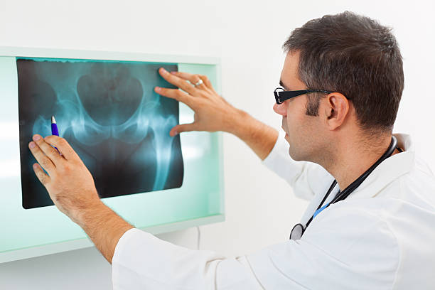 Mid adult doctor examining X-ray image Mid adult doctor examining X-ray image of a pelvis in the hospital. sacrum stock pictures, royalty-free photos & images
