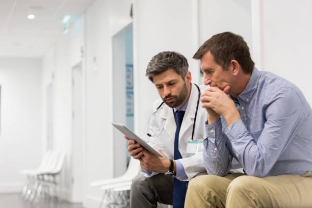 Médico de mediana edad explicando al paciente serio sobre la tableta digital en el hospital - foto de stock