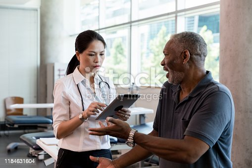 The mid adult female doctor uses the digital tablet to input the mature adult male patient's concerns.