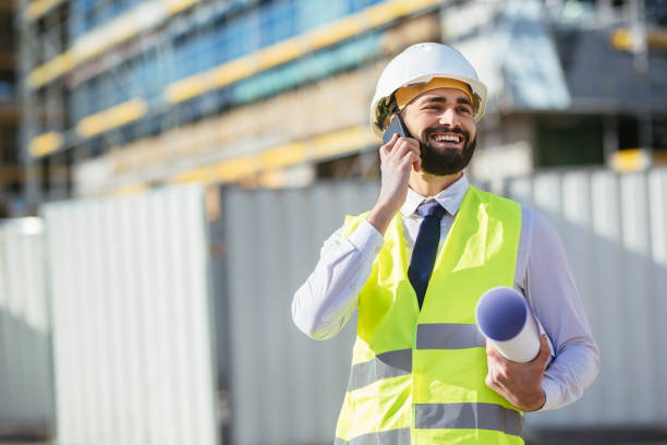 Mid adult engineer holding blueprint and talking on mobile phone stock photo
