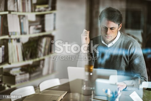 Mid adult businessman reading an e-mail on laptop at home office. The view is through glass.