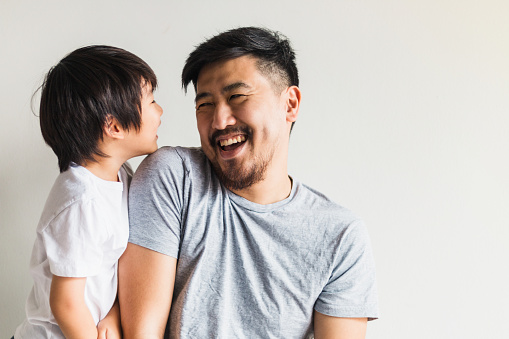 Mid adult father and preschool son share laugh