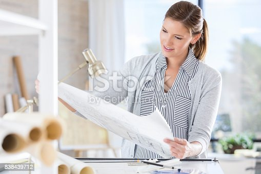 istock Mid adult female architect holds up blueprint for review 838439712