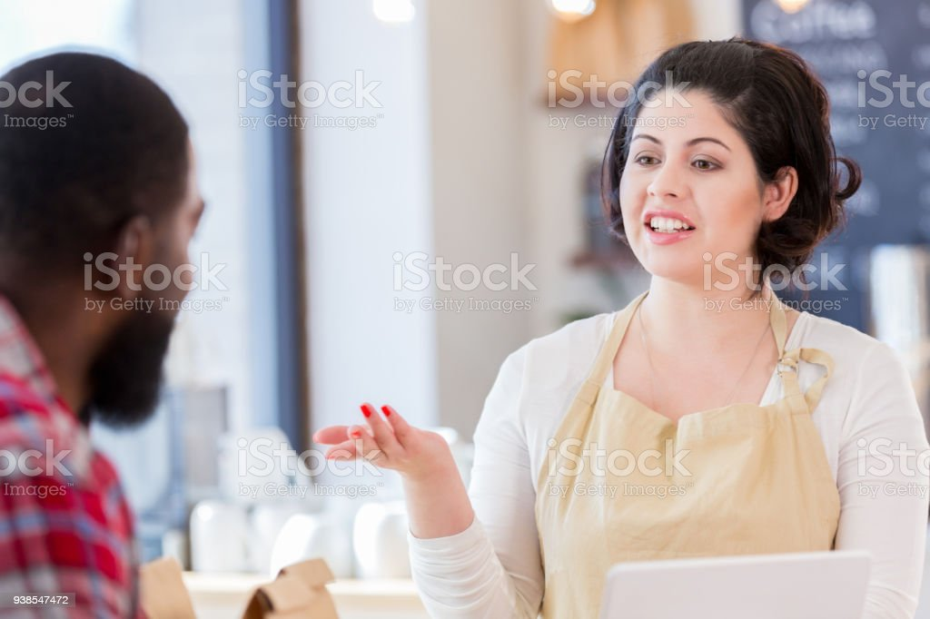 Mid adult female Caucasian barista lists coffee specials for customer stock photo