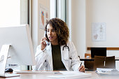 Sitting in her office, the mid adult female doctor calls for exam results before speaking to the patient.  She also consults her desktop computer.