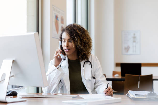 Mid adult female doctor calls about exam results stock photo