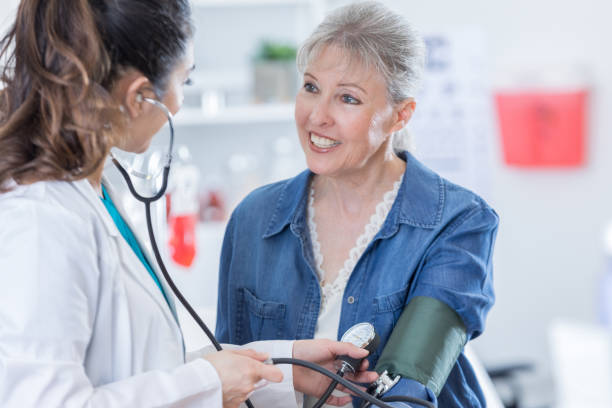 Mid adult female doctor check's patient's blood pressure stock photo