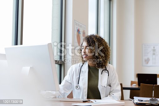 The mid adult female doctor reviews her patient's records on her computer in her office.