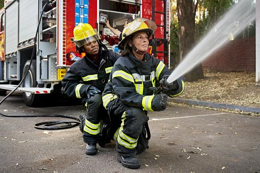 Full length view of Black firefighter providing backup for Hispanic teammate holding nozzle shooting straight stream of water.