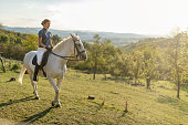 Mid adult female owner riding a horse in nature