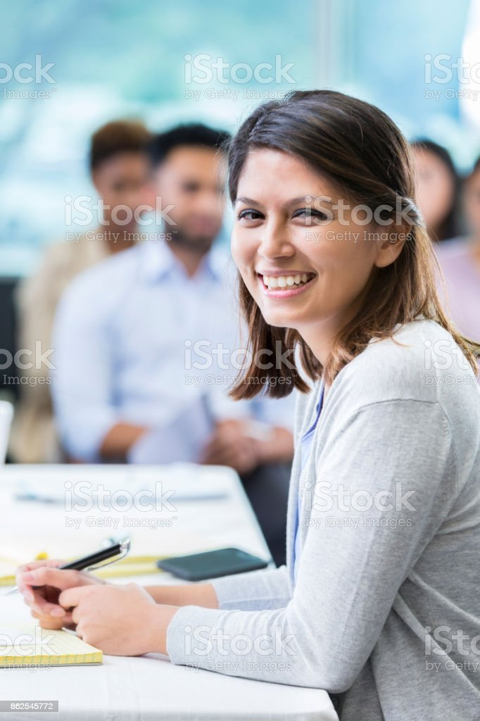 Mid adult female professor smiles for camera during business lecture stock photo