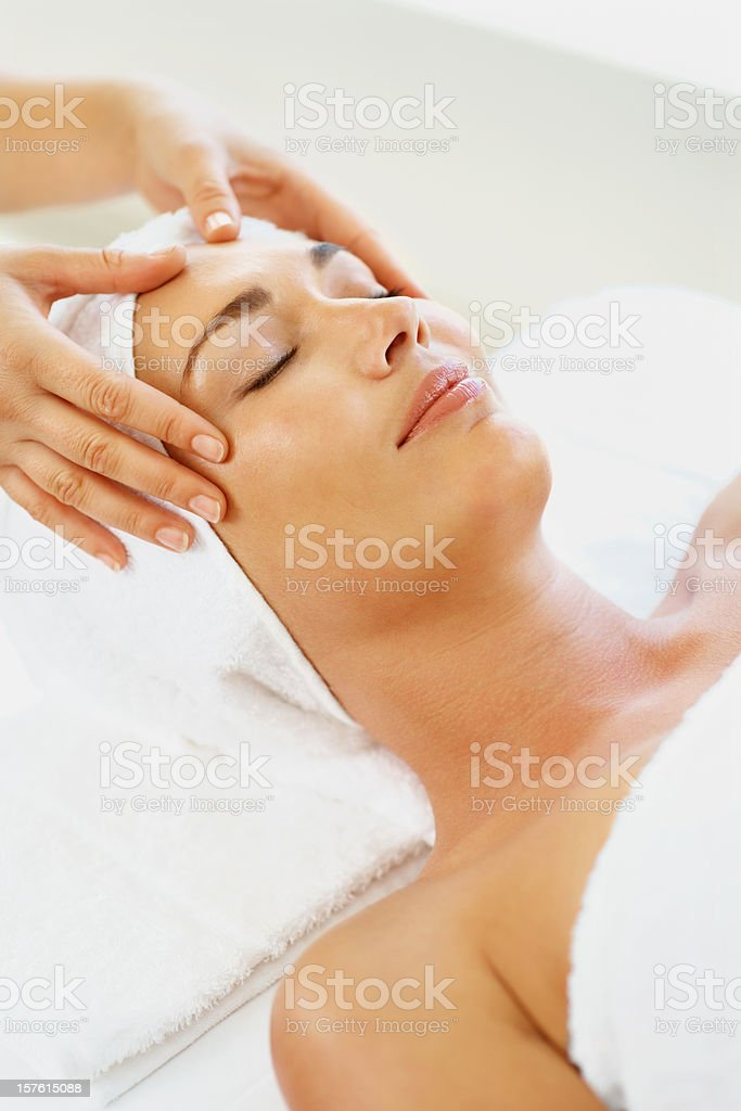 Mid adult female receiving facial massage in spa royalty-free stock photo