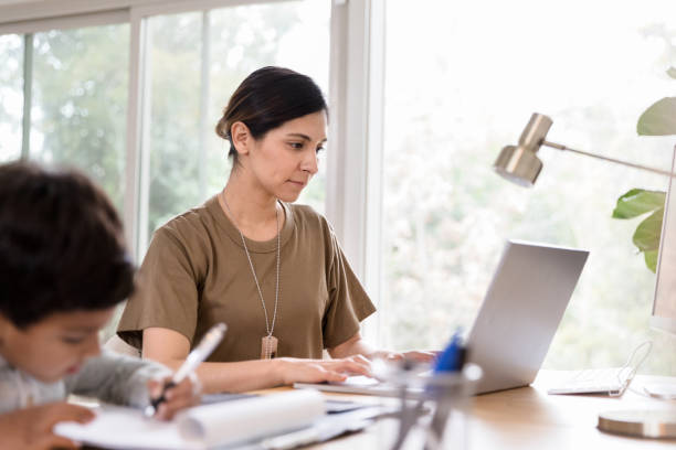 Mid adult female soldier works on home finances A mid adult female soldier concentrates while using a laptop in her home office. Her son is drawing a picture in the foreground. military lifestyle stock pictures, royalty-free photos & images