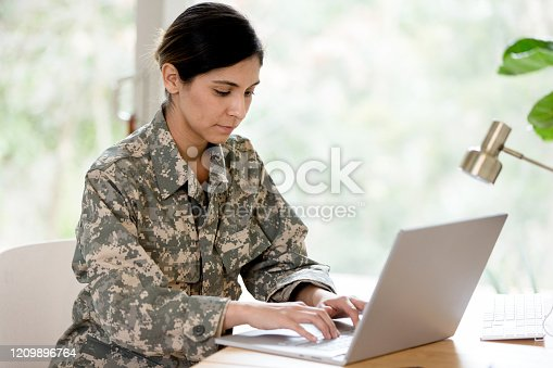 A mid adult female soldier wearing her uniform works on her laptop at home.