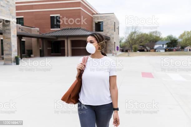 Mid adult female teacher walks by empty school during epidemic picture id1220169477?b=1&k=6&m=1220169477&s=612x612&h=qnz7sqj k0ncqkjglkyio1fitvz6bcofofa1fk7hlgu=