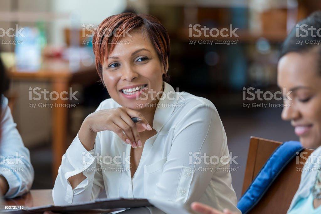 Mid adult female university student enjoys library study group stock photo