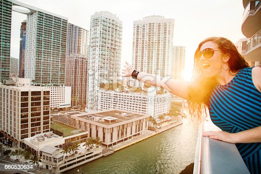 Mid adult female waving to the city on balcony in Miami Florida. The Miami river and downtown Brickell area with its office and apartment towers can be seen in the background.