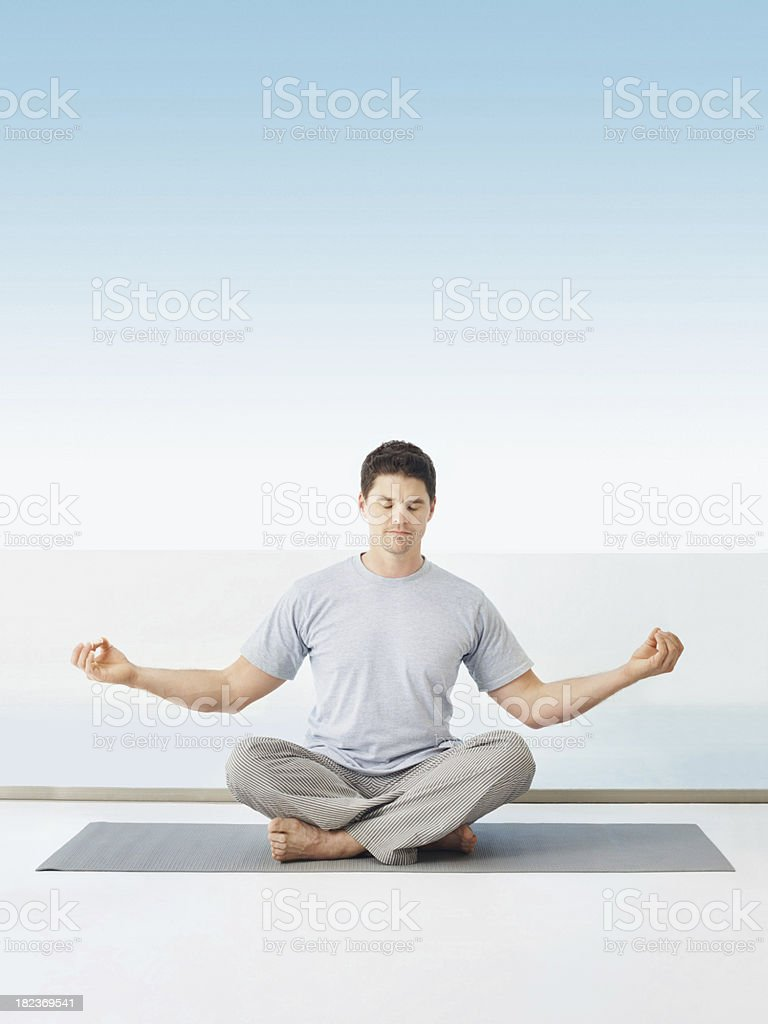 Mid adult guy practicing yoga at home royalty-free stock photo