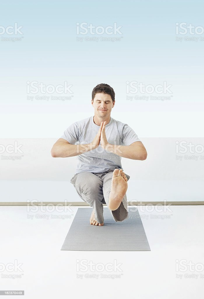 Mid adult guy practicing yoga home royalty-free stock photo