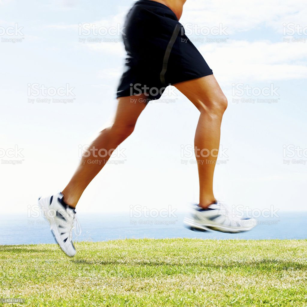 Mid adult guy running on grass against sky royalty-free stock photo