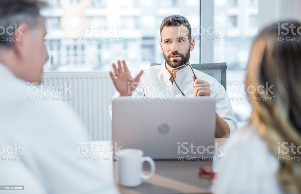 Mid adult healthcare worker having a meeting with his colleagues. stock photo