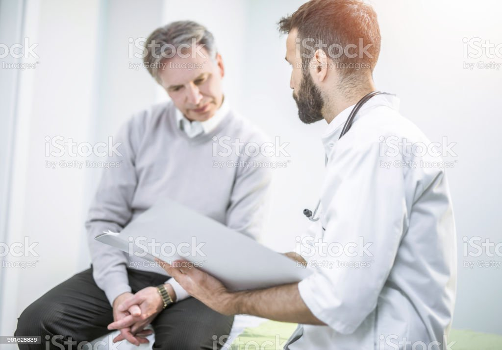 Mid adult healthcare worker showing medical results to his senior patient. stock photo