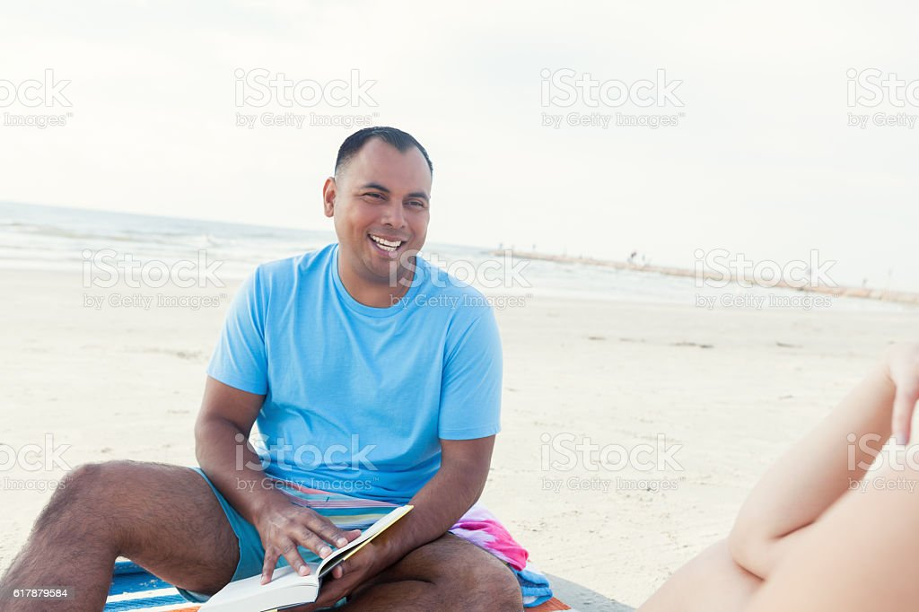 Mid adult Hispanic husband talks with wife on the beach stock photo