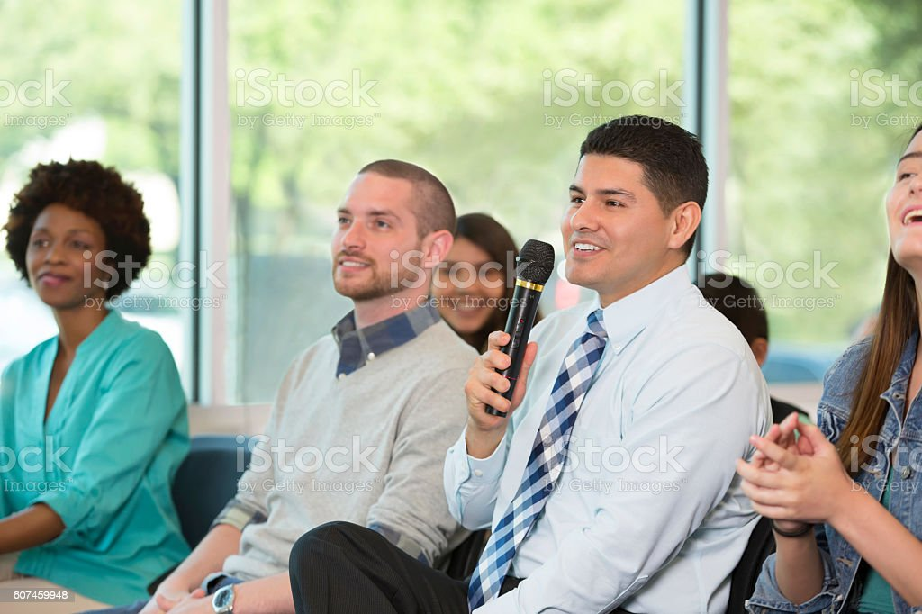 Mid adult Hispanic man asks question at town hall meeting stock photo