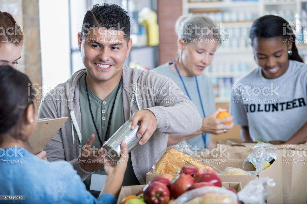 Mid adult Hispanic man volunteers during food drive stock photo