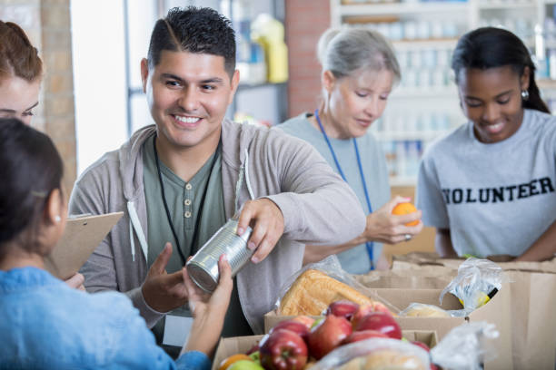 Mid adult Hispanic man volunteers during food drive stock photo