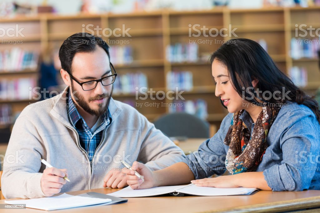 Mid adult Hispanic students working on college assignment in library stock photo
