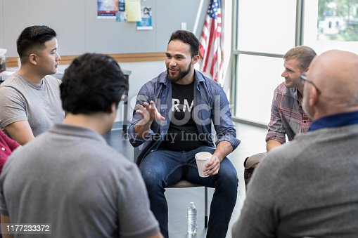 Mid adult Hispanic male veteran gestures as he discusses something during a veterans group meeting in a community center.