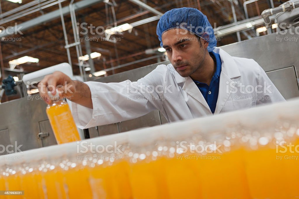 Mid adult industrial worker looking at bottle in factory stock photo