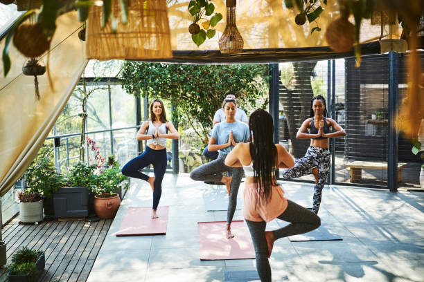 Mid adult instructor teaching tree pose to people Mid adult instructor teaching tree pose to people. Multi-ethnic athletes are exercising during yoga class. They are in sports clothing. yoga class stock pictures, royalty-free photos & images