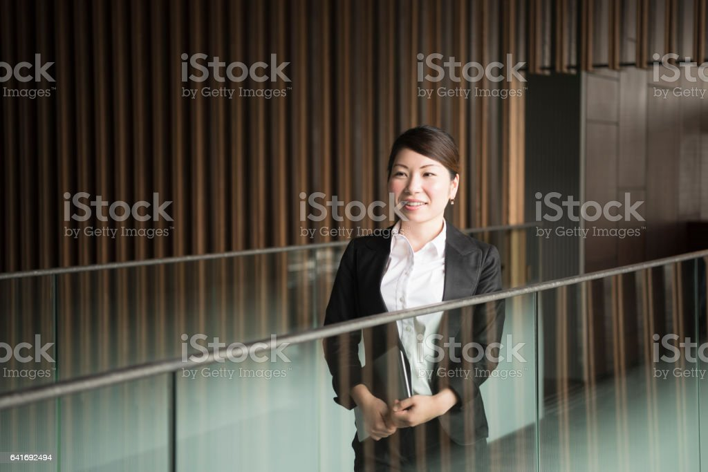Mid adult Japanese businesswoman by railings in modern office stock photo