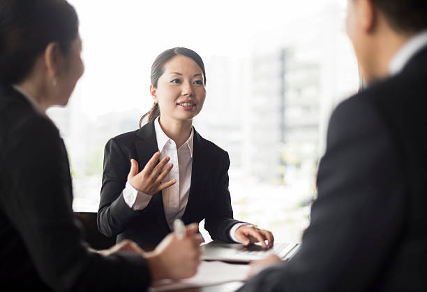 mid adult japanese businesswoman in meeting with colleagues, gesturing - 身ぶり ストックフォトと画像