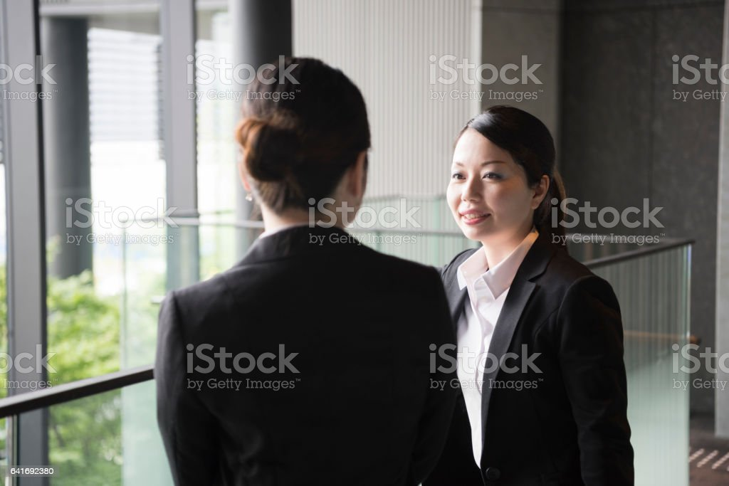 Mid adult Japanese businesswoman in modern office building, talking stock photo