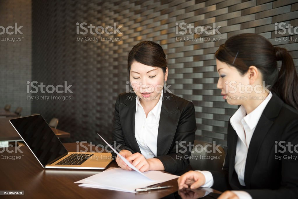 Mid adult Japanese businesswoman showing colleague document stock photo