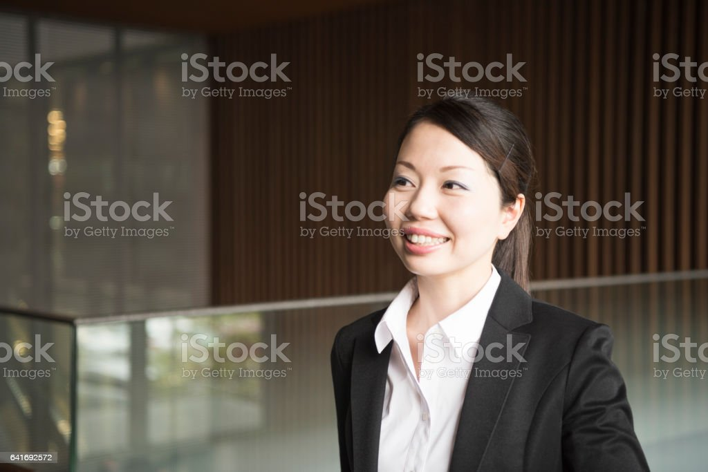 Mid adult Japanese businesswoman smiling and looking away stock photo