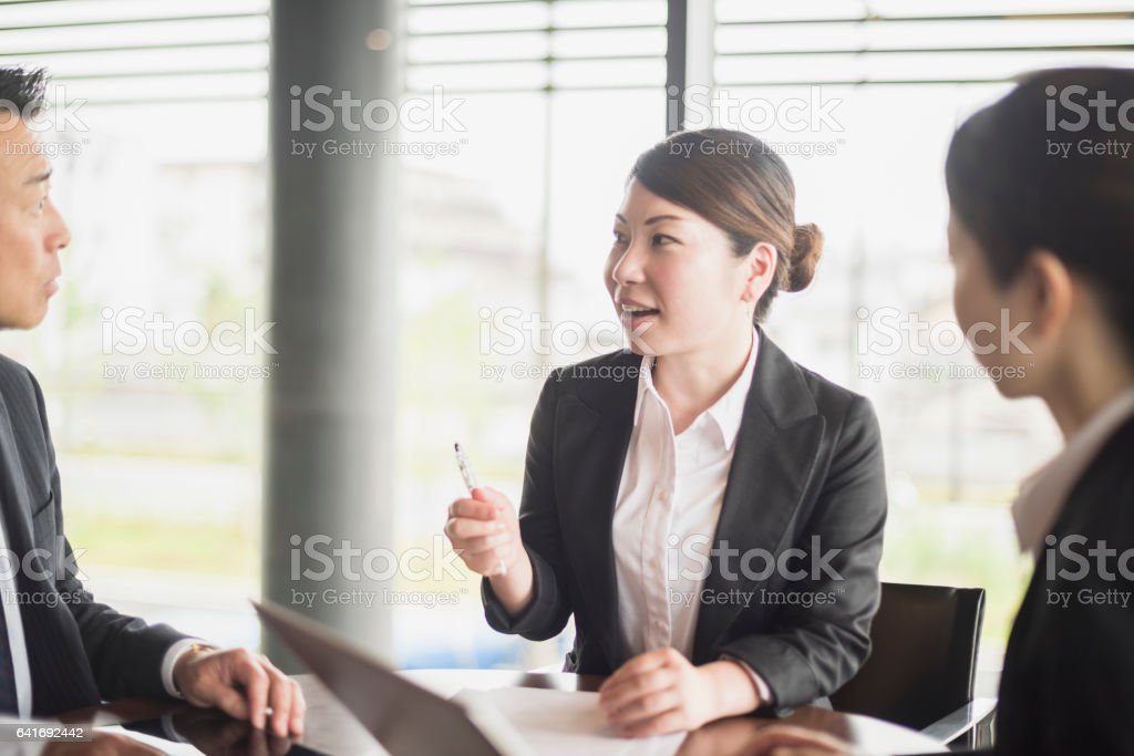 Mid adult Japanese businesswoman talking to colleague, smiling stock photo