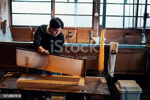 Mid adult man making paper using the traditional Japanese method of screening pulp and fiber.
