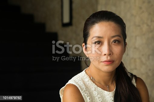 Mid adult Japanese woman indoors pensive and sad house portrait with a large dark staircase in the background.