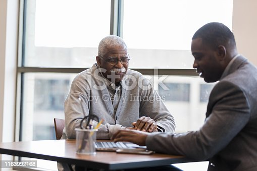 The mid adult loan officer patiently and cheerfully help sthe senior man find the best investment option for retirement savings.