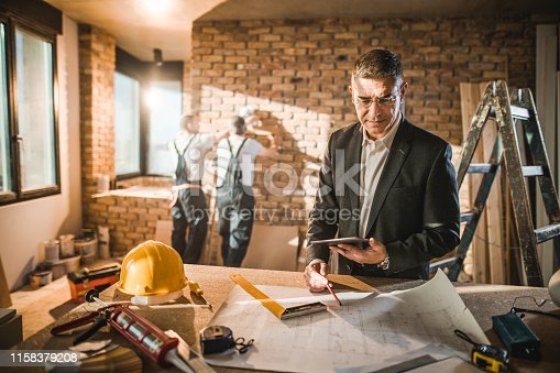 512113530 istock photo Mid adult male architect going through housing plan at construction site. 1158379208